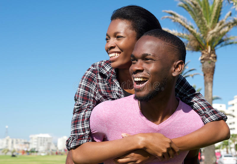 Glücklicher junger Mann, der attraktive Freundin auf seinem zurückbringt stockbilder