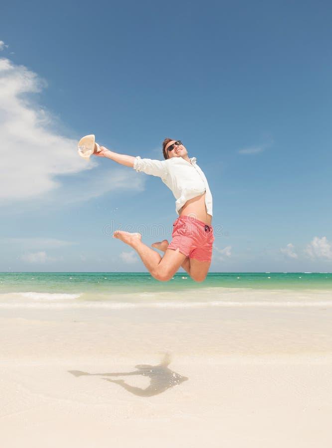 Glücklicher junger Mann, der auf den Strand springt lizenzfreies stockfoto