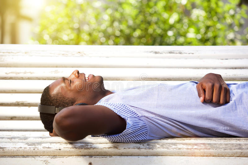 Glücklicher junger Mann, der auf Parkbank mit Kopfhörern liegt stockfoto