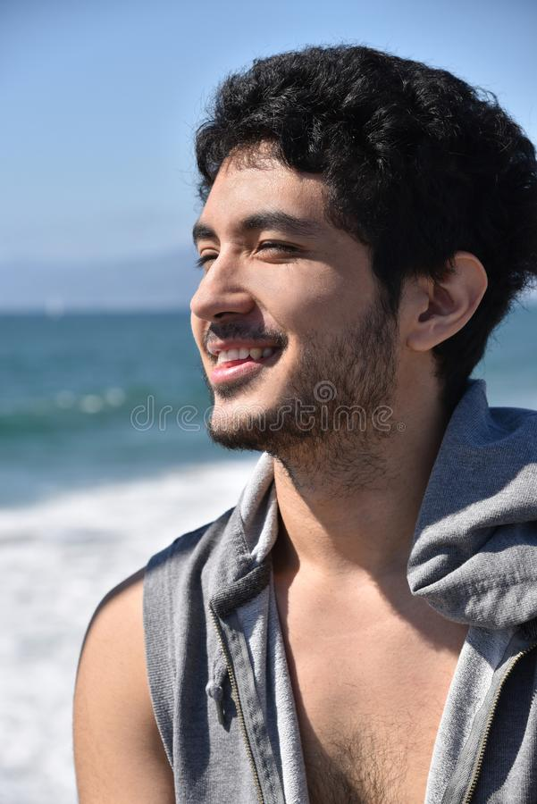 Glücklicher junger Mann, der den Ozean übersieht stockbild