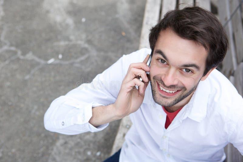 Glücklicher junger Mann, der draußen durch Handy nennt stockbilder