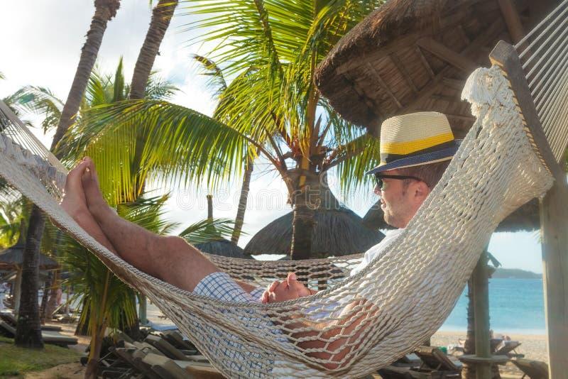 Glücklicher junger Mann, der in einer Hängematte auf dem Strand stillsteht lizenzfreie stockfotografie
