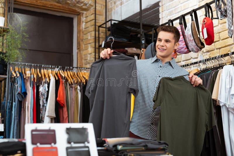 Glücklicher junger Mann, der Einkaufen- und Holding zwei T-Shirts tut stockfoto