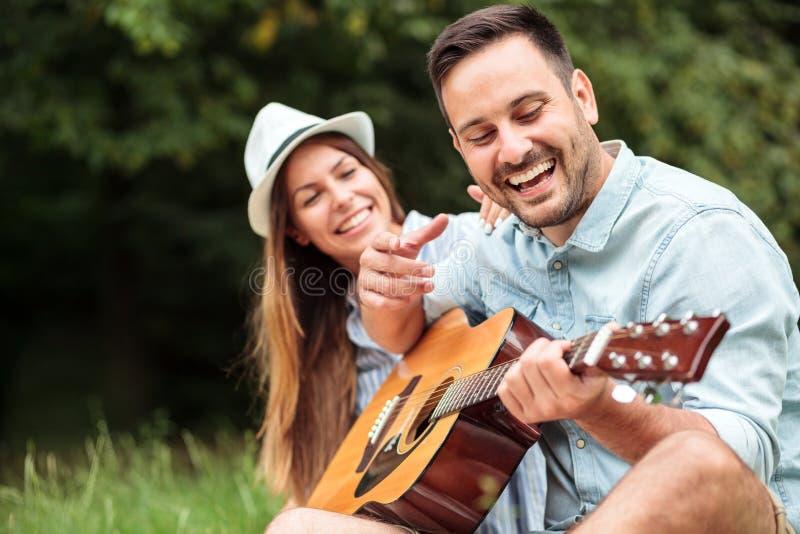 Glücklicher junger Mann, der Gitarre zu seiner schönen Freundin spielt lizenzfreies stockbild