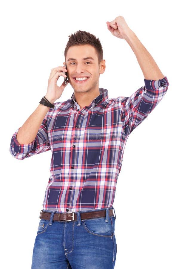 Glücklicher junger Mann, der große Nachrichten empfängt lizenzfreies stockfoto