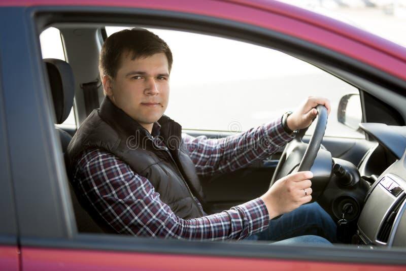 Glücklicher junger Mann, der kleines Auto fährt lizenzfreies stockfoto