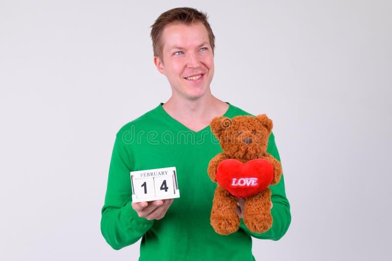 Glücklicher junger Mann, der mit Abreißkalender und Teddybären für Valentinstag denkt lizenzfreies stockbild