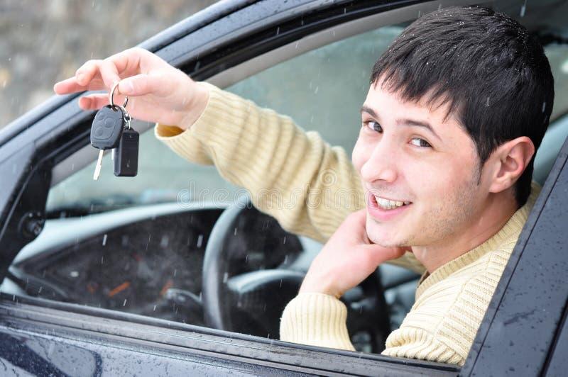 Glücklicher junger Mann, der seine Autotasten zeigt lizenzfreie stockfotos
