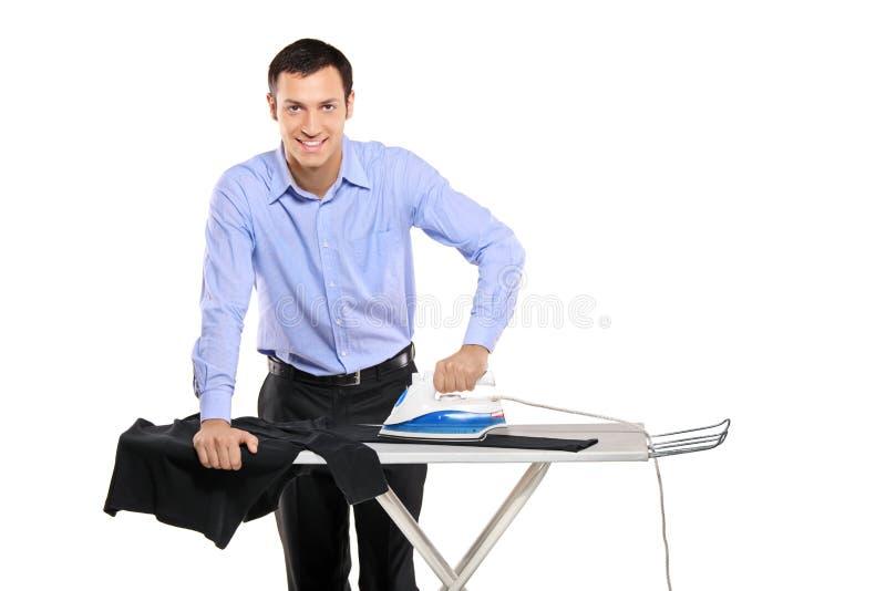 Glücklicher junger Mann, der seine Kleidung bügelt lizenzfreie stockfotos