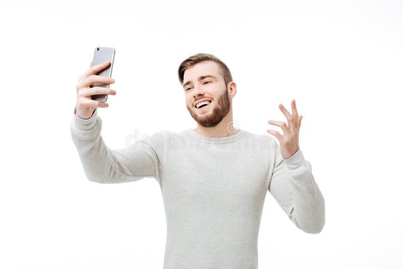 Glücklicher junger Mann, der selfie nimmt und warum Geste über weißem Hintergrund zeigt lizenzfreies stockfoto