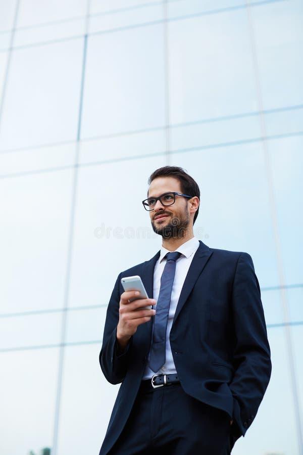 Glücklicher junger Mann in einer stilvollen Klage und in Sonnenbrille, die vor Büros mit Telefon stehen lizenzfreie stockbilder