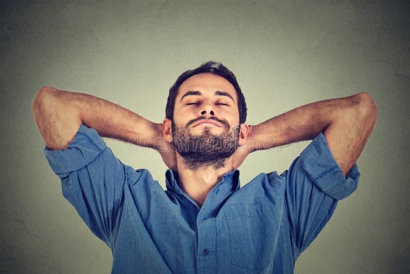 Glücklicher junger Mann im blauen Hemd, das aufwärts im entspannenden oder Nickerchen machenden Gedanken schaut lizenzfreie stockfotografie