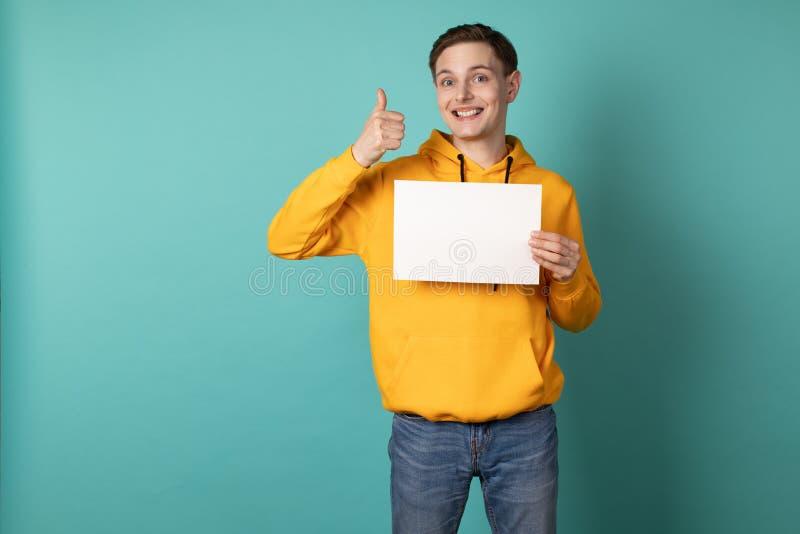 Glücklicher junger Mann im gelben Hoodie lokalisiert über blauem Hintergrund stockfoto