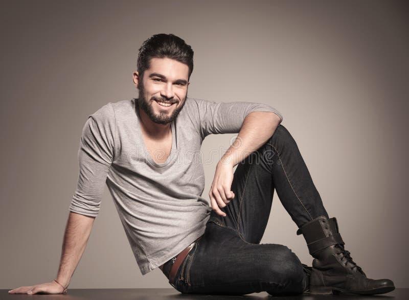 Glücklicher junger Mann sitzt auf dem Boden und lächelt stockfotos