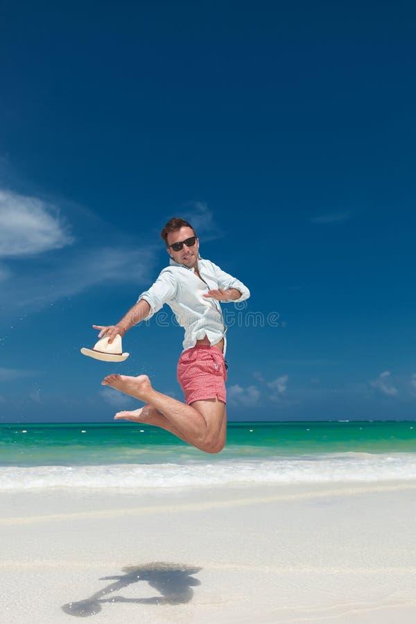 Glücklicher junger Mann springt für Freude auf dem Strand stockfotografie