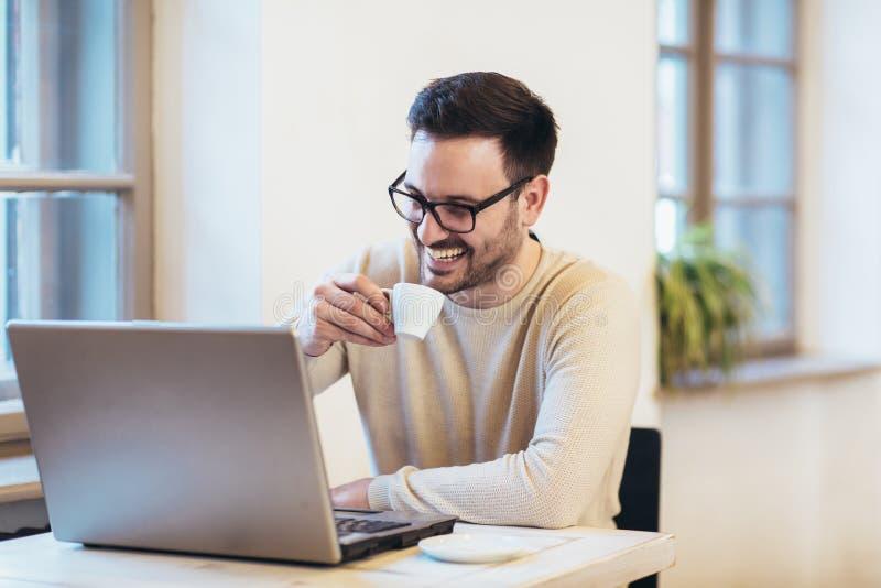 Glücklicher junger Mann, tragende Gläser und Lächeln, wie er an seinem Laptop arbeitet stockfotografie