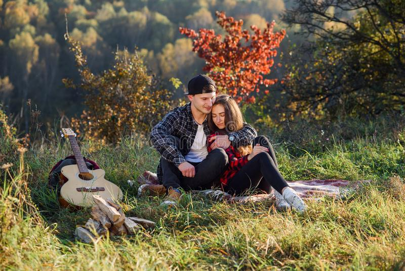 Glücklicher junger Mann umarmt seine Freundinweichheit und Habenrest auf Picknick im Park Paare in der Liebe, die Rest an hat stockbild