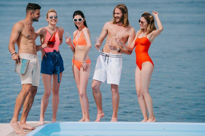glücklicher junger Mann und Freundinnen, die Champagner am Poolside trinken stockfoto