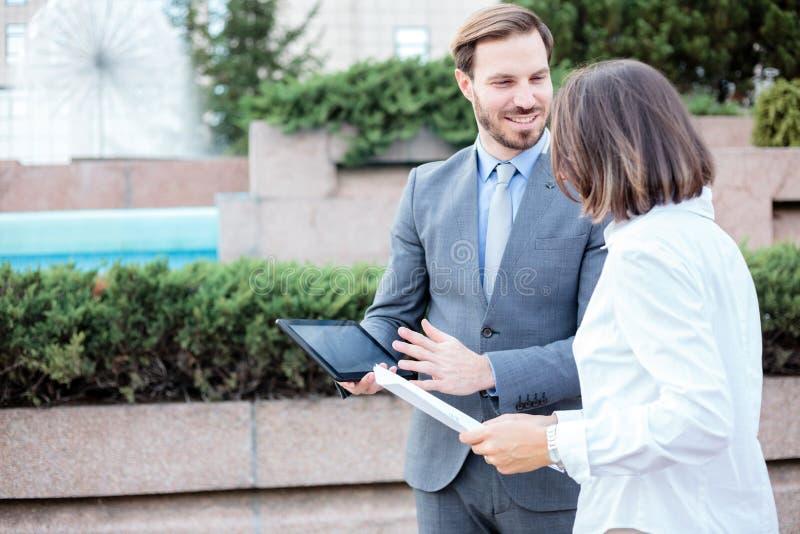 Glücklicher junger Mann und weibliche Geschäftsleute, die vor einem Bürogebäude, eine Sitzung und eine Diskussion habend sprechen lizenzfreie stockfotos
