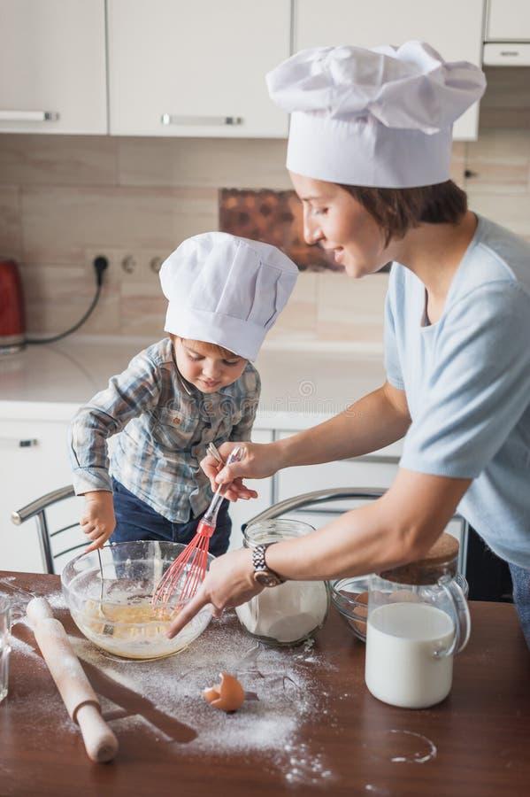 glücklicher junger mischender Teig der Mutter und des Kindes mit Schneebesen stockbilder