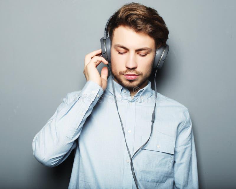Glücklicher junger stilvoller Mann, der sein Kopfhöreranzeige lächelndes wh justiert lizenzfreies stockfoto