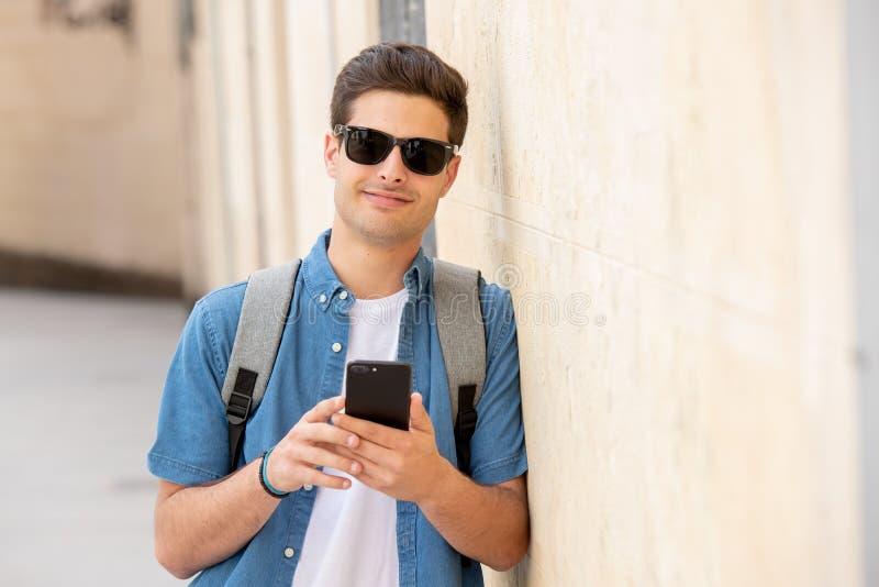 Glücklicher junger Studentenmann, der an seinem intelligenten Telefon in der modernen Stadt simst stockfotografie