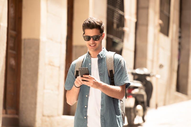 Glücklicher junger Studentenmann, der an seinem intelligenten Telefon in der modernen Stadt simst stockbilder