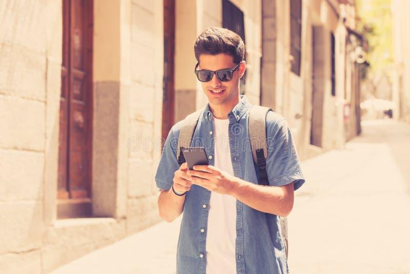 Glücklicher junger Studentenmann, der an seinem intelligenten Telefon in der modernen Stadt simst lizenzfreie stockbilder