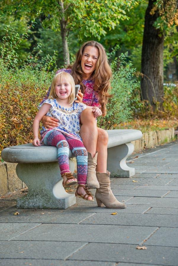 Glücklicher junger Unterhaltungshandy der Mutter und des Babys im Stadtpark stockfoto