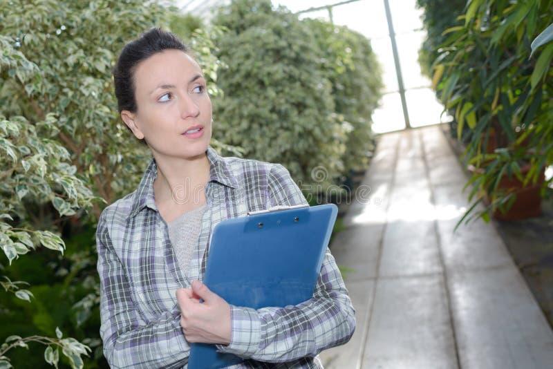 Glücklicher junger weiblicher Gärtner, der Klemmbrett am Gewächshaus hält stockbilder