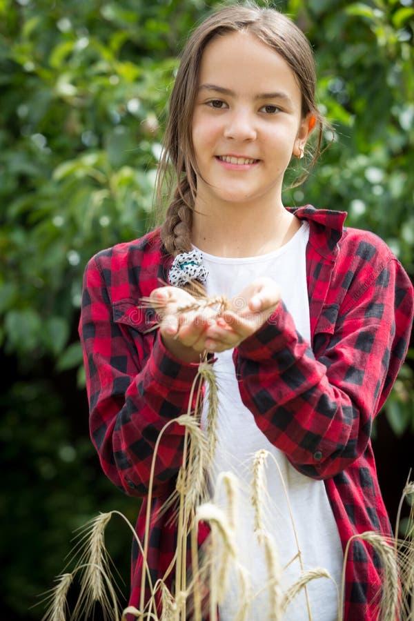 Glücklicher junger weiblicher Landwirt, der auf dem Weizengebiet am sonnigen Tag aufwirft stockbilder