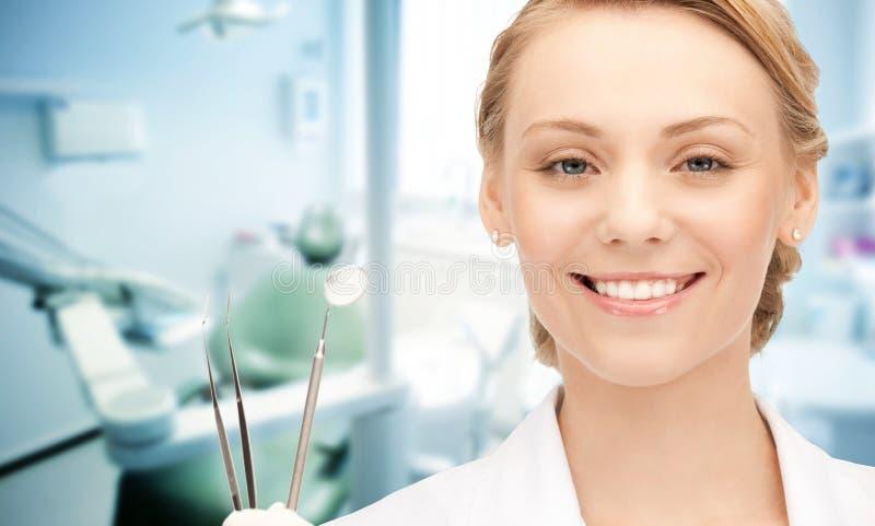 Glücklicher junger weiblicher Zahnarzt mit Werkzeugen stockfotos