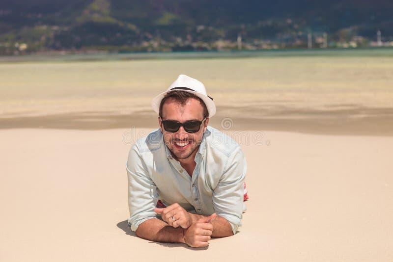 Glücklicher junger zufälliger Mann, der auf einem weißen Sandstrand liegt stockfotografie