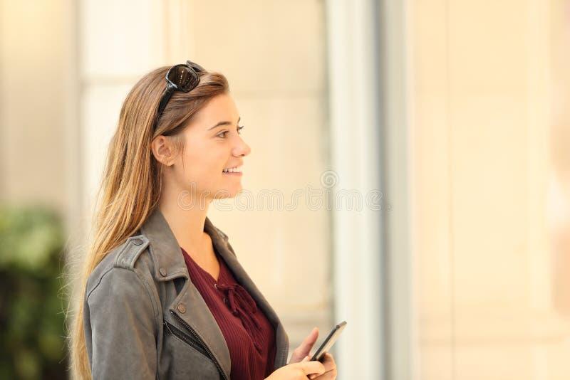 Glücklicher Käufer, der ein Schaufenster aufpasst, ein intelligentes Telefon zu halten stockfotografie