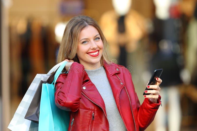 Glücklicher Käufer, der Taschen halten und Telefon, das Kamera betrachtet stockbilder