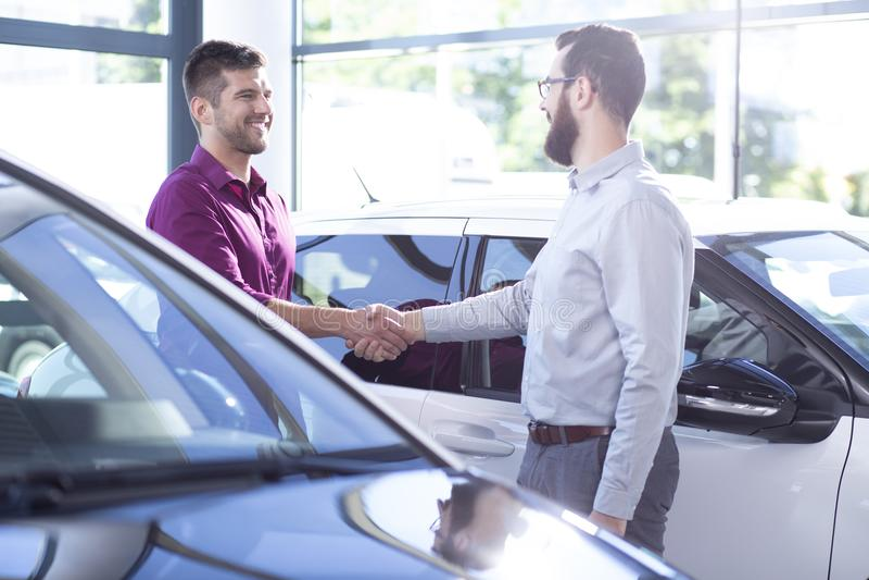Glücklicher Käufer des Neuwagens Hände mit Händler nach Geschäft im Salon rüttelnd lizenzfreie stockfotos
