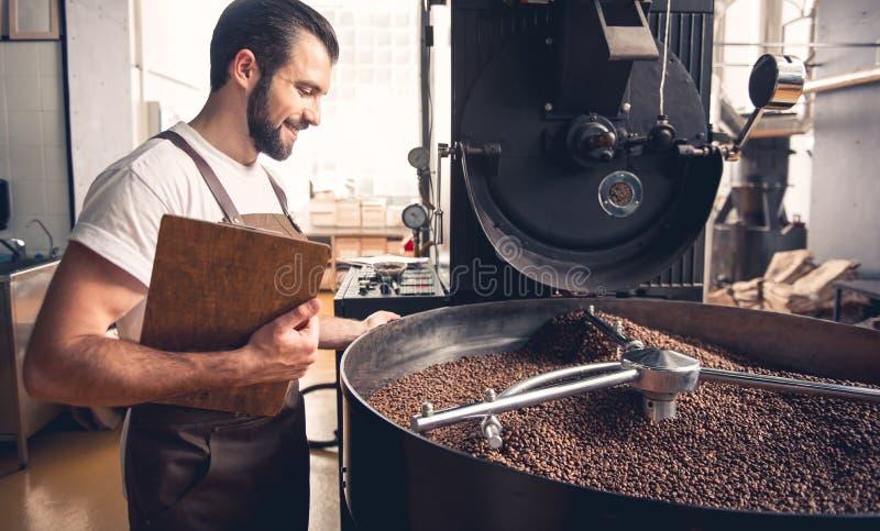 Glücklicher Kaffeeröster, der Bohnen zubereitend steuert stockbild