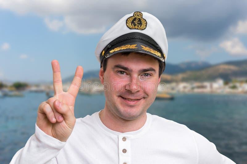 Glücklicher Kapitän mit der Seemannkappe, die Siegeszeichen zeigt lizenzfreie stockbilder