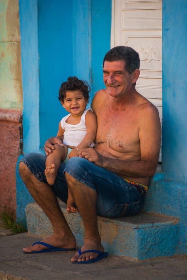 Glücklicher karibischer alter kolonialmann und Kind mit klassischem Haus und Wand der Stadtmenschen in Trinidad, Kuba, Amerika stockbild