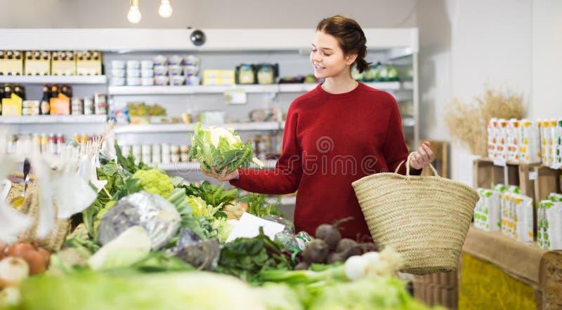 Glücklicher kaufender Blumenkohl des jungen Mädchens am Markt stockfotos
