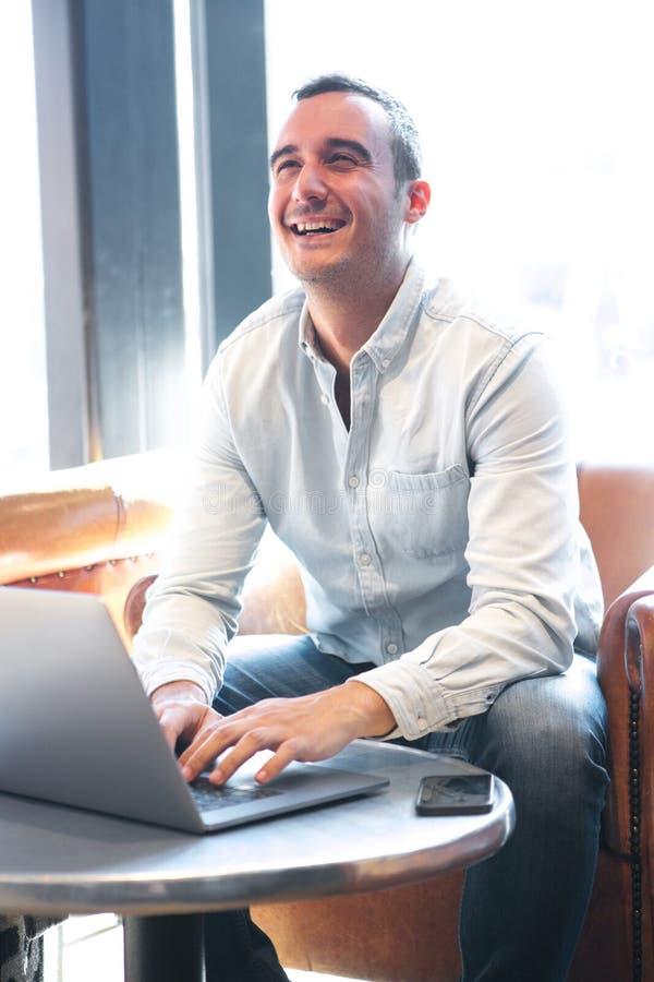 Glücklicher Kerl, der am Café unter Verwendung der Laptop-Computers sitzt stockfotos