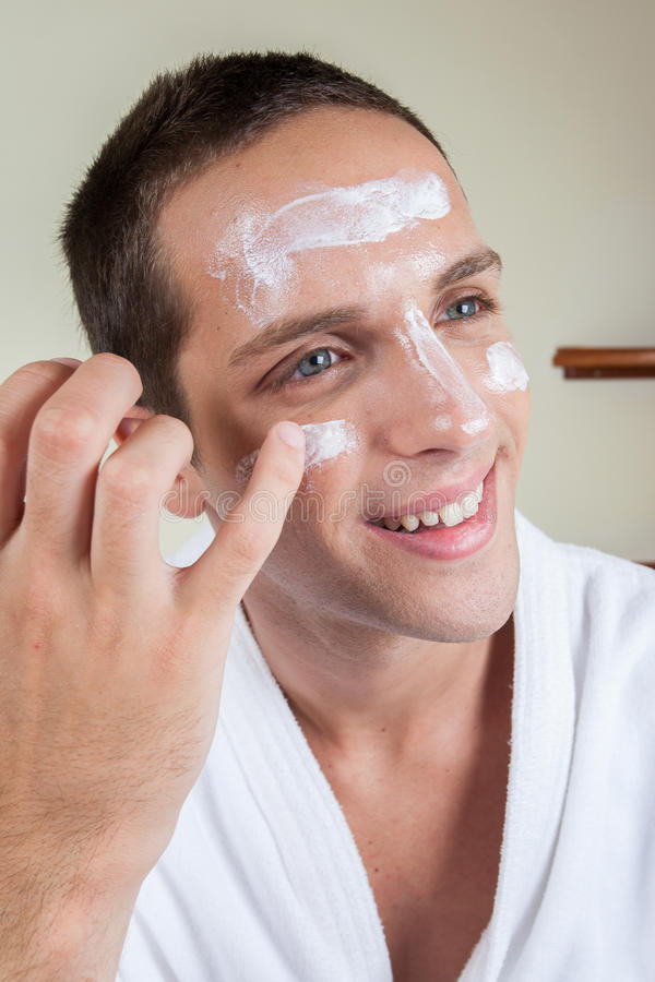 Glücklicher Kerl, der Gesichtscreme mit Ihrem Finger setzt lizenzfreie stockfotografie