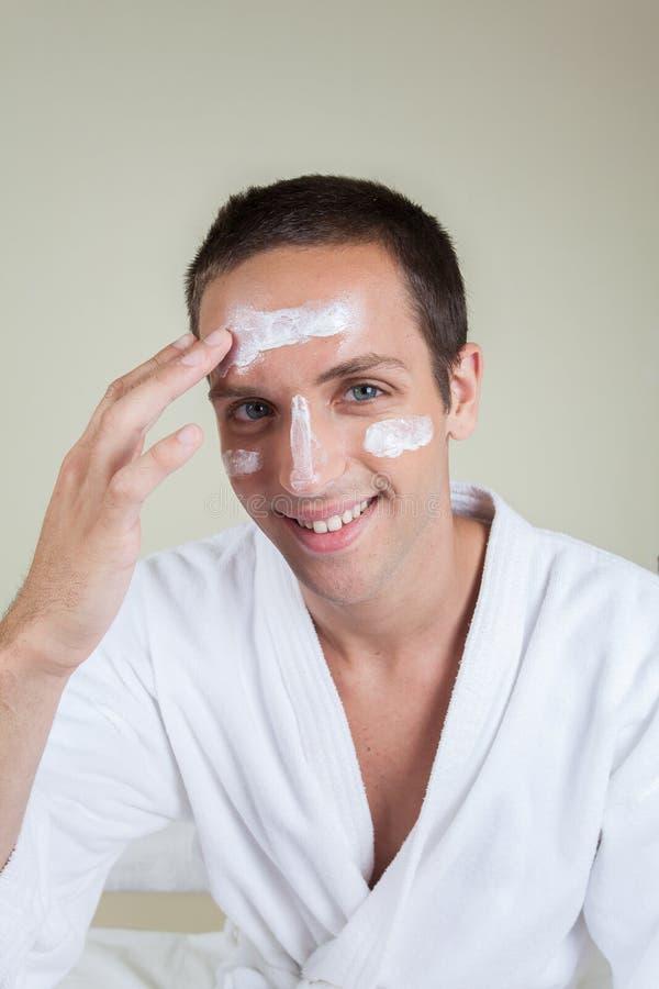 Glücklicher Kerl mit Gesichtscreme stockfoto
