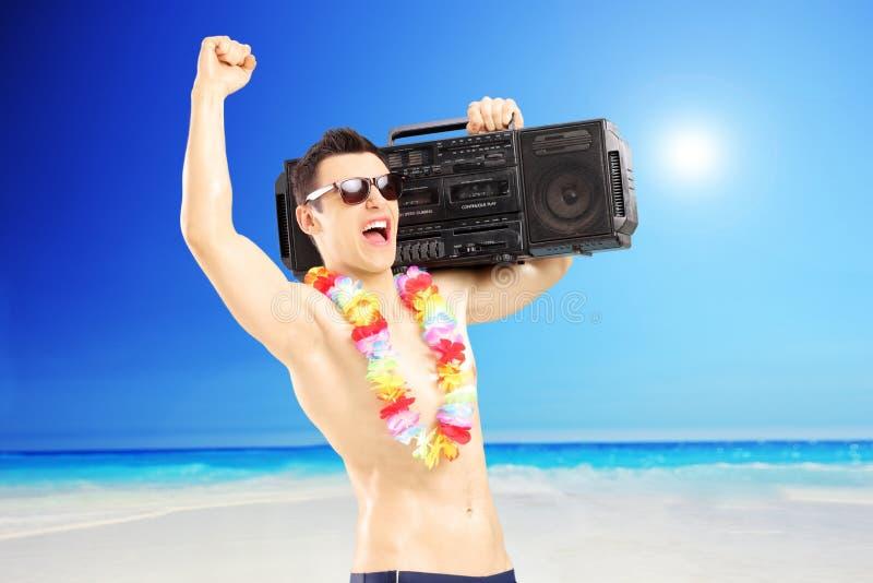 Glücklicher Kerl mit Radio auf seiner Schulter Glück nahe bei gestikulierend lizenzfreies stockfoto