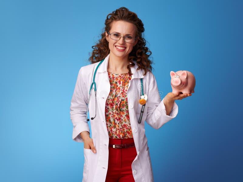 Glücklicher Kinderarztdoktor, der Sparschwein auf Blau hält lizenzfreie stockbilder