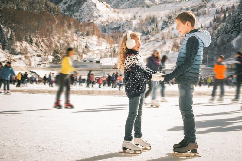 Glücklicher Kindereislauf an der Eisbahn im Freien lizenzfreie stockfotos