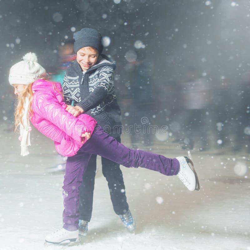 Glücklicher Kindereislauf an der Eisbahn im Freien, Eiskunstlauf stockbild