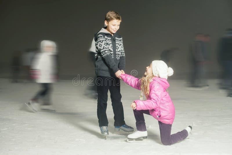 Glücklicher Kindereislauf an der Eisbahn, Winternacht stockfotografie