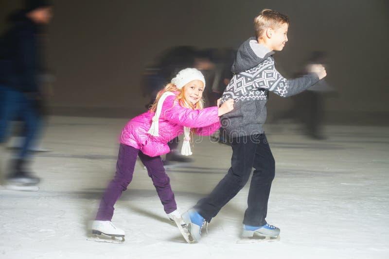 Glücklicher Kindereislauf an der Eisbahn, Winternacht lizenzfreies stockfoto