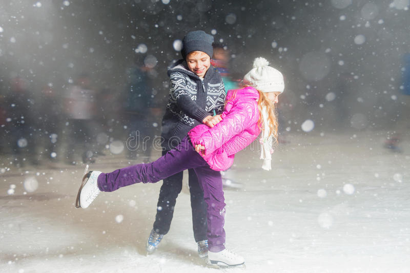 Glücklicher Kindereislauf an der Eisbahn, Winternacht lizenzfreies stockbild